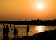 Silhouettes of tourists near sea and beach town in rays of orange sunset Royalty Free Stock Images