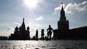 Silhouettes of tourists visiting Moscow Kremlin, Red square and Saint Basil's cathedral. Taking photos and posing. 4K. Unrecognizable tourists visiting Moscow stock video