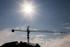 Silhouettes of tower crane at construction side. Over sun at sunrise, cloud with blue sky of background stock photos