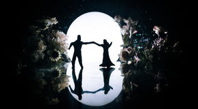 Silhouettes of toy couple dancing under the Moon at night. Figures of man and woman in love dancing at moonlight Royalty Free Stock Image