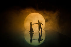 Silhouettes of toy couple dancing under the Moon at night. Figures of man and woman in love dancing at moonlight Stock Image