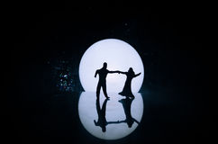 Silhouettes of toy couple dancing under the Moon at night. Figures of man and woman in love dancing at moonlight Royalty Free Stock Photos