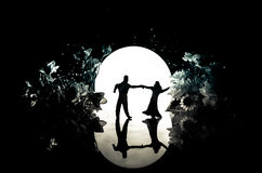 Silhouettes of toy couple dancing under the Moon at night. Figures of man and woman in love dancing at moonlight Stock Photo