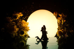 Silhouettes of toy couple dancing under the Moon at night. Figures of man and woman in love dancing at moonlight Royalty Free Stock Photography