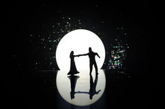 Silhouettes of toy couple dancing under the Moon at night. Figures of man and woman in love dancing at moonlight Stock Photos