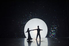 Silhouettes of toy couple dancing under the Moon at night. Figures of man and woman in love dancing at moonlight Stock Photography