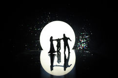 Silhouettes of toy couple dancing under the Moon at night. Figures of man and woman in love dancing at moonlight Stock Images