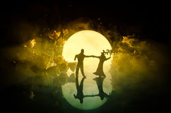 Silhouettes of toy couple dancing under the Moon at night. Figures of man and woman in love dancing at moonlight Royalty Free Stock Photo