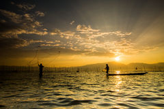 Silhouettes of the traditional fishermen throwing fishing net du Stock Images