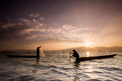 Silhouettes of the traditional fishermen throwing fishing net du Royalty Free Stock Photos