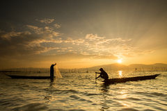 Silhouettes of the traditional fishermen throwing fishing net du Stock Photography