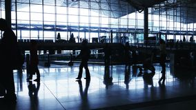 Silhouettes of Travelers in Airport. Beautiful wide panoramic view of the main hall of an airport stock video footage