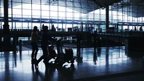 Silhouettes of Travelers in Airport. Wide view of the main hall of an airport stock video footage