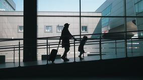 Silhouettes of travelers - mother and little daughter going down the gate at the airport at background large window. Close up stock footage