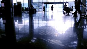 Silhouettes of travelers passengers in airport transit terminal walking with luggage baggage going traveling.  stock footage