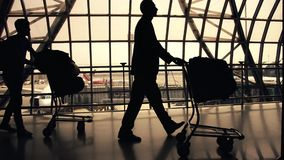 Silhouettes of travellers in airport. Silhouette of airline passengers in an airport stock footage