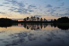 Silhouettes of trees and colorful sky are reflected in the forest lake in the evening. Unusual and picturesque scene. Russia. Silhouettes of trees and colorful stock images
