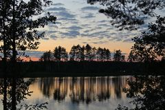 Silhouettes of trees and colorful sky are reflected in the forest lake in the evening. Unusual and picturesque scene. Russia. Silhouettes of trees and colorful stock photography