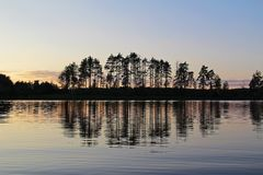 Silhouettes of trees and colorful sky are reflected in the forest lake in the evening. Unusual and picturesque scene. Russia. Silhouettes of trees and colorful stock image