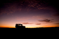 Silhouettes of truck on horizon at sunrise Stock Photos