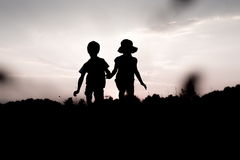 Silhouettes of twins jumping off a cliff at sunset. Silhouettes of kids jumping off a cliff at sunset. Little boy and girl jump high holding hands. Brother and stock photos