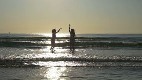 Silhouettes of two beautiful girlfriends having fun and playing in the ocean in slow motion stock footage