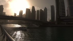 Silhouettes of two boats passing under the bridge on the waterfront of Dubai Marina at sunset stock video