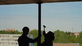 Silhouettes of two builders. Silhouettes of two workers with metal beam stock footage