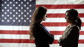 Silhouettes of two business women on the background of the American flag. Duel of views