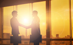 Silhouettes two businessmen handshake in cooperation agreement c. Oncept at office and successful business partner. business man shaking hands to seal a deal Stock Image
