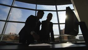 Silhouettes of two businessmen working with a computer on a window background in a big bright office. HD video stock footage