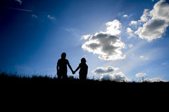 The silhouettes of two children holding hands on the top one hill. And the clear sky with some clouds Stock Image