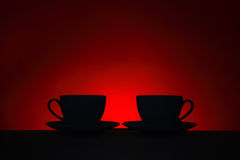 Silhouettes of two coffee cups on red background Royalty Free Stock Image