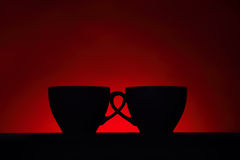 Silhouettes of two coffee cups on red background Stock Photography