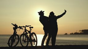 Silhouettes of two cyclists at sunset. Doing selfie. Silhouettes of two cyclists at sunset. The pair finished the bike ride on the river and do selfi on a stock video