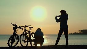 Silhouettes of two cyclists at sunset. The pair finished the bike ride. On the river bank. Romantic couple at sunset. Silhouette of bicycles on sunset stock footage