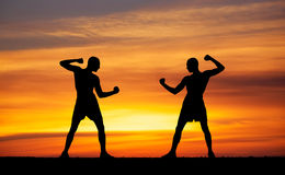 Silhouettes of two fighters on sunset Royalty Free Stock Photo