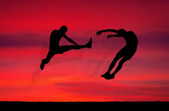 Silhouettes of two fighters on sunset fiery background. Royalty Free Stock Photography