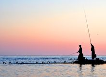 Silhouettes of two fishermen Stock Photography