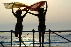Silhouettes of two girls dancing with scarfs. Silhouettes of two young girls with scarfs dancing on a brige at sunset Stock Image