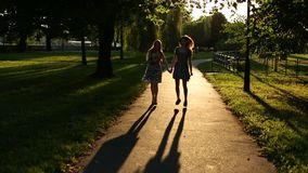 Silhouettes of two girls walking in the alley. stock video
