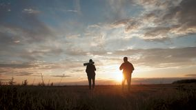 Silhouettes of two hikers with backpacks enjoying sunset view from top of a mountain. Enjoying the sunset view from stock footage