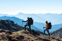 Silhouettes of two Hikers in front of Morning Mountains View. Silhouettes of two Hikers staying on rocky and grassy Ridge with Backpacks and other Gear Stock Images