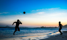 Silhouettes of two jumping men playing beach football at Copacabana, Rio de Janeiro Royalty Free Stock Photography