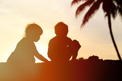 Silhouettes of two kids play at sunset beach Royalty Free Stock Photo