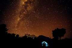 Silhouettes of two lovers in tent. starry sky royalty free stock photography