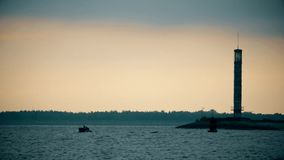 Silhouettes of two men in a boat near lighthouse at dusk. In the morning or evening stock video footage