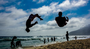 Silhouettes of two men performing somersaults at Ipanema beach Stock Images