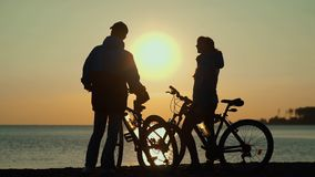 He silhouettes of two people on the beach with bikes. Sunset on the sea. Sun reflected in water. Man and woman with bicycles. Silhouettes of cyclists at sunset stock footage