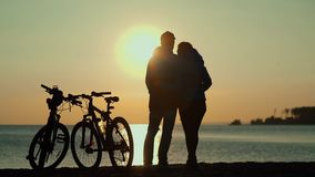 The silhouettes of two people with bicycles on the beach. Sunset on the sea. Sun reflected in water. Man and woman with bicycles. Silhouettes of cyclists at stock video